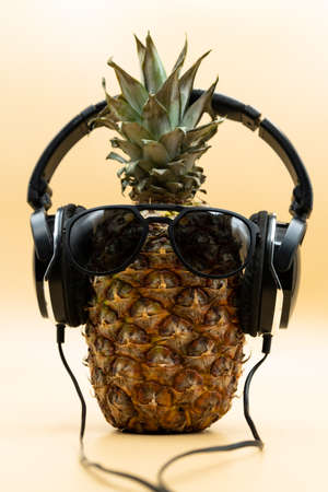 Closeup of cool pineapple in sunglasses wearing headphones looking at camera over pastel yellow background. Party concept