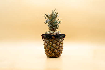 Isolated funny pineapple in sunglasses looking at camera over pastel yellow background. Summertime concept