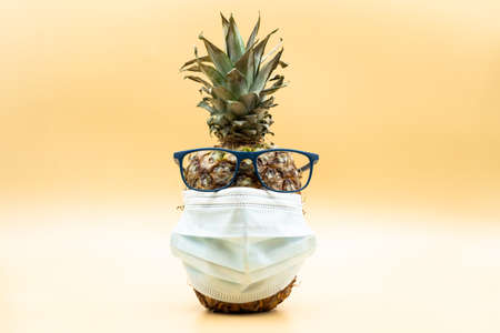 Closeup of a pineapple in face mask wearing glasses looking at camera over pastel yellow background. Covid-19 concept