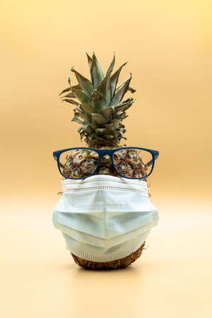 Weird pineapple with face mask wearing glasses looking at camera over pastel yellow background. Covid-19 concept