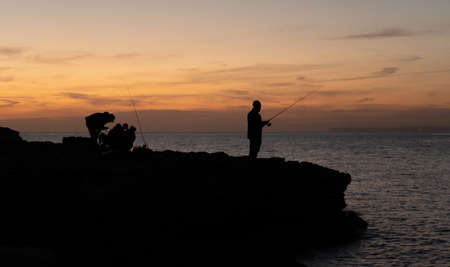 Silhouette of fisherman with another group behind him at sunset in front of the sea. Fishing concept Standard-Bild