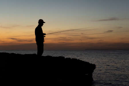 A fisherman with the rod at sunset against the light in Majorca, Spain. Fishing concept Standard-Bild