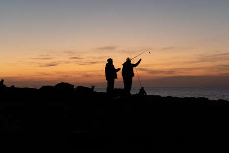 Silhouettes of two fishermen getting ready at sunset in front of the sea in Majorca. Fishing concept