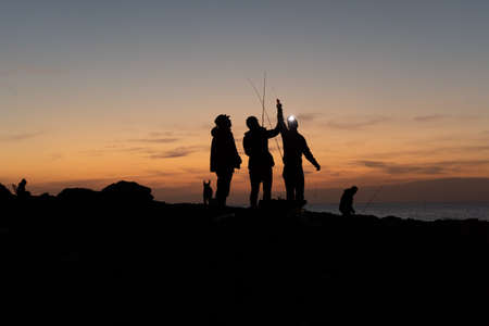 Group of fishermen preparing the rods at sunset in Majorca. Fishing concept
