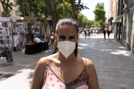Millennial woman portrait wearing face mask looking at camera in the street. Covid-19 concept Standard-Bild