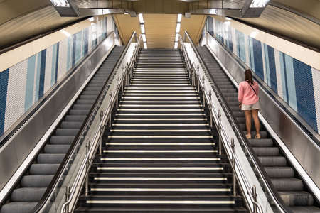View of escalators with a staircase in the center in the subway and a woman on her back going up one of the escalators. Transport concept