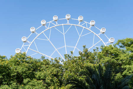 View of half a Ferris wheel that looks over some trees in the foreground with blue sky. Amusement park concept