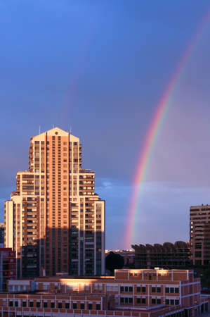 Vertical image of a tall building in Valencia with a rainbow next to it. Weather concept
