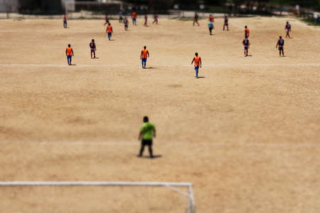 Amateur soccer match on a dirt field in a neighborhood with the tilt shift effect applied to the image. Amateur sport concept Standard-Bild
