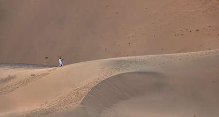 A Saudi couple take a selfie in the huge sand dunes in Badr, Medina, Saudi Arabia. Tourism in KSA
