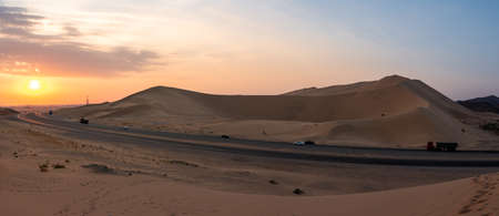 Sand dunes in Badr, Madinah, Saudi Arabia at sunset with the highway running through them. Tourism in KSA