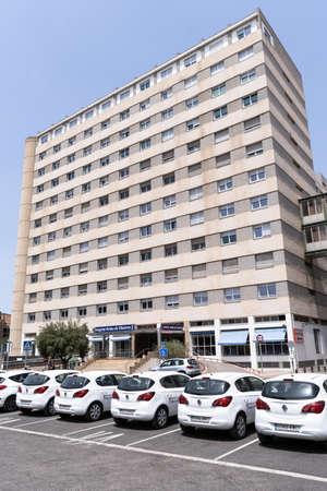 Valencia, Spain -July 24, 2021: Facade of the Arnau de Vilanova public Hospital in Valencia with health service cars in the foreground