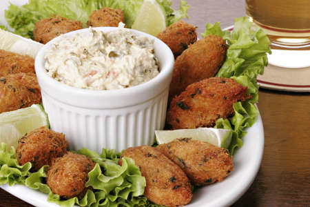 Cod fish cakes (croquettes) with chunky tartar sauce.  Typical dish made up of potatoes, bacalhau (codfish), eggs and parsley. Also known as