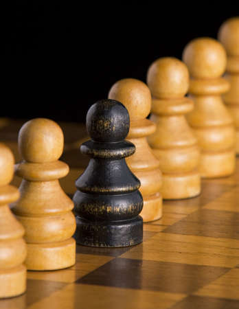 Wooden black chess pawn among white pawns on a wooden chess board