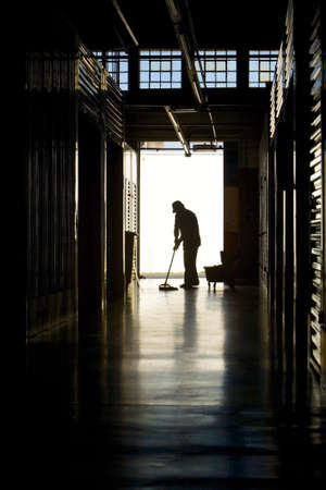 Silhouette of a man moping warehouse floor