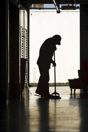 backlit: Silueta de un piso de almac�n moping de hombre