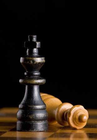 Wooden black King standing next to defeated white Queen on chessboard with black background. Stock Photo