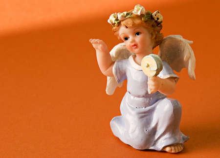 Angel figurine on an orange background Stock Photo