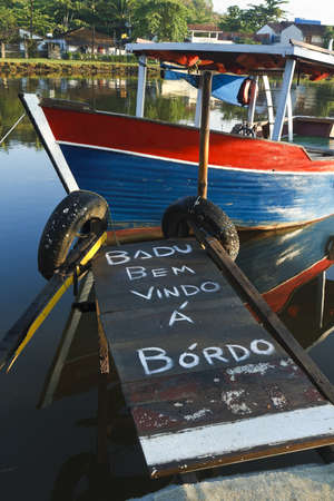 Welcome aboard message written in Portuguese on a gangplank leading to a wooden boat in Paraty, Brazil. Stock Photo