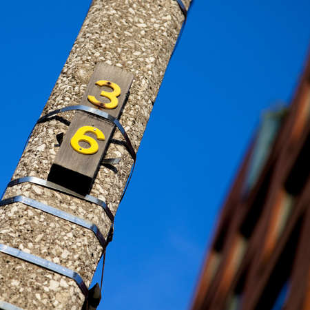 number 36: Concrete post with a small wooden plaque with number 36 on it. Stock Photo