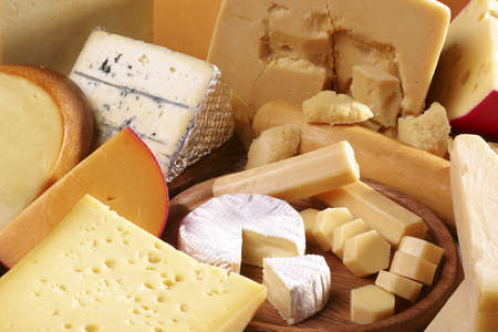 Assorted cheeses in diferent shapes and sizes Imagens