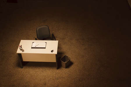 Single office desk in a empty room with dark grey office chair