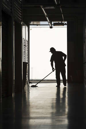 warehouse: Silhouette of a man moping warehouse floor