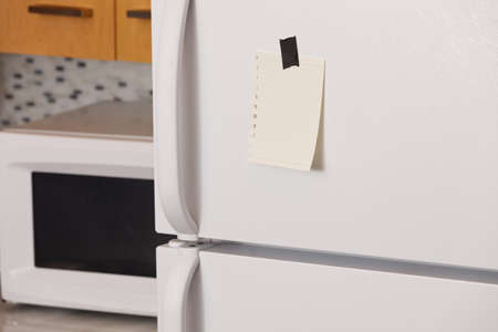 written communication: Piece of yellow paper taped to a refrigerator door Stock Photo
