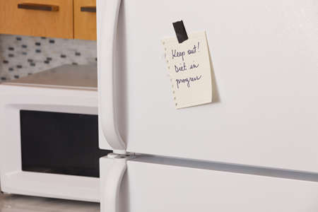 Piece of yellow paper taped to a refrigerator door saying: