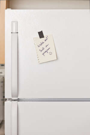 Piece of yellow paper taped to a refrigerator door Stock Photo - 9304009