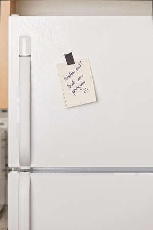 nevera: Pieza de papel amarillo grabado a una puerta de frigor�fico Foto de archivo