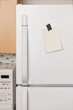 Piece of yellow paper taped to a refrigerator door Stock Photo - 9304006