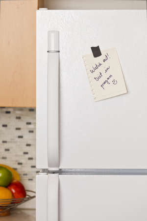 Piece of yellow paper taped to a refrigerator door photo