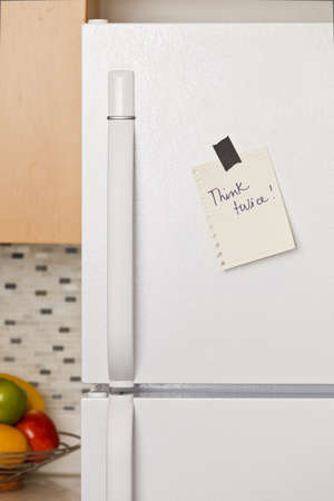 Piece of yellow paper taped to a refrigerator door Stock Photo - 9304007