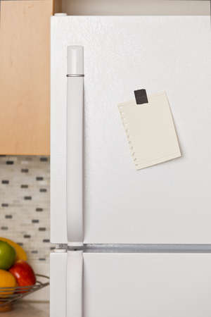 fridge: Piece of yellow paper taped to a refrigerator door Stock Photo