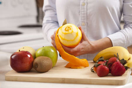 Woman in the kitchen peeling fruits