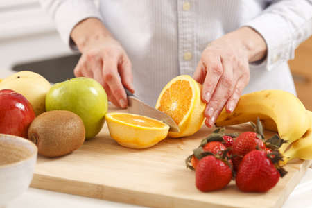 Woman in the kitchen cutting fruits