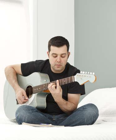 Man composing music using electric-acousitc guitar Stock Photo