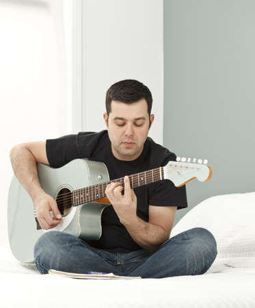 Man composing music using electric-acousitc guitar Stock Photo