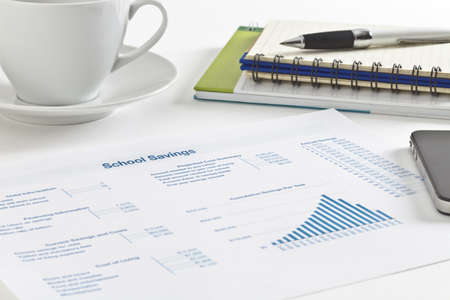 Sheet of paper with figures, tables and graph, small notebook and pen, cell phone and a cup of tea Stock Photo - 9533677