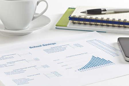 document management: Vel papier met cijfers, tabellen en grafiek, kleine notebook en pen, mobiele telefoon en een kopje thee