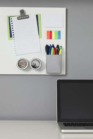 흰색 사무실 책상, 노트북 컴퓨터와 회색 벽에 흰색 자석 보드 스톡 콘텐츠