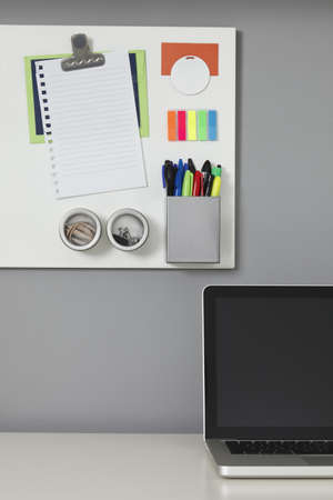White office desk, laptop computer and a white magnetic board on a gray wall photo