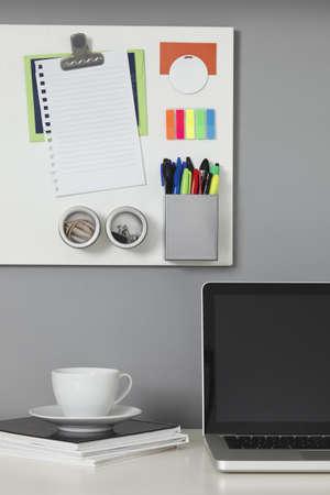 Witte kantoor bureau, een laptop computer en een wit magnetisch bord op een grijze muur