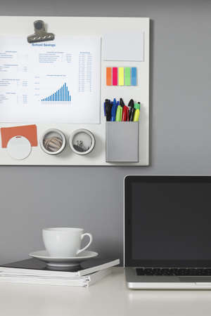 White office desk, laptop computer and a white magnetic board on a gray wall Stock Photo - 9633568