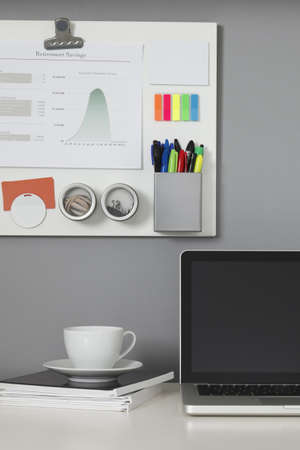 White office desk, laptop computer and a white magnetic board on a gray wall Stock Photo - 9633563