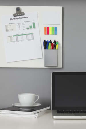 White office desk, laptop computer and a white magnetic board on a gray wall Stock Photo - 9633560