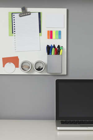 office space: White office desk, laptop computer and a white magnetic board on a gray wall