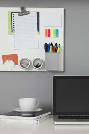 Witte Bureau, laptopcomputer en een witte Magneetbord op een grijze muur