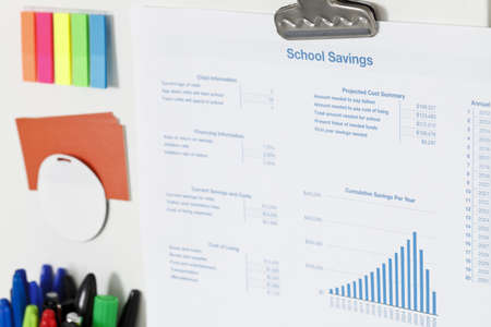 Printout of a Schoo Savings spreadsheet, charts and tables, stuck on a white magnetic board Stock Photo